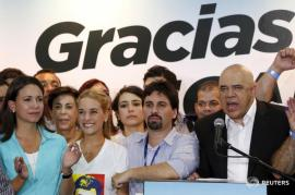 "Jesus Torrealba (R), secretary of the Venezuelan coalition of opposition parties (MUD), speaks near Lilian Tintori (2nd L), wife of jailed Venezuelan opposition leader Leopoldo Lopez during a news conference in Caracas December 7, 2015. Venezuela's opposition won control of the legislature from the ruling Socialists for the first time in 16 years on Sunday, giving them a long-sought platform to challenge President Nicolas Maduro. The banner reads, ""Thanks"". REUTERS/Carlos Garcia Rawlins - RTX1XI04"